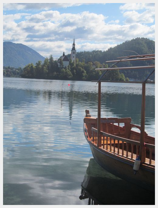 An iconic picture of Lake Bled island and a pletna boat.