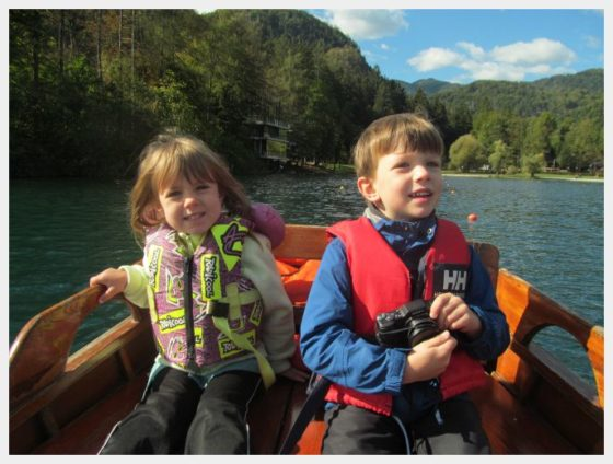 The kids sitting in the row boat.  Rowing out to the lake was one of our favorite things to do in Lake Bled.