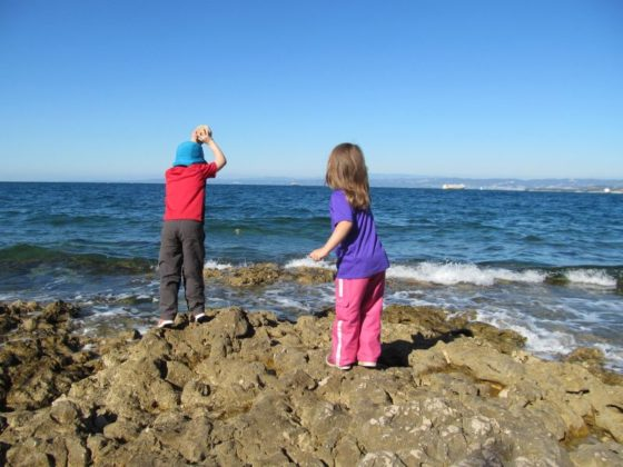 The kids throwing rocks into the water in Izola, Slovenia.